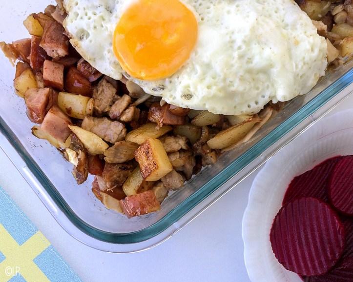 Schaal met gebakken aardappelblokjes, stukjes vlees en ui met erop een spiegelei. Ernaast een schaaltje zoetzure bietjes.