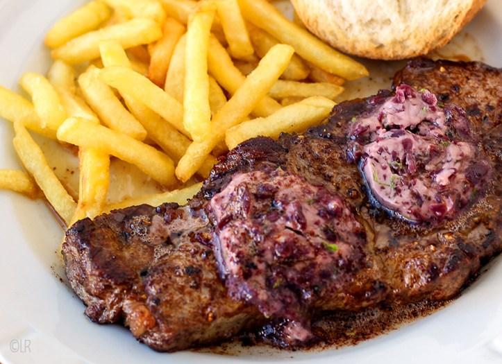 Een mooie biefstuk met daarop twee schijfjes wijnkoopmansboter geserveerd met friet en brood.