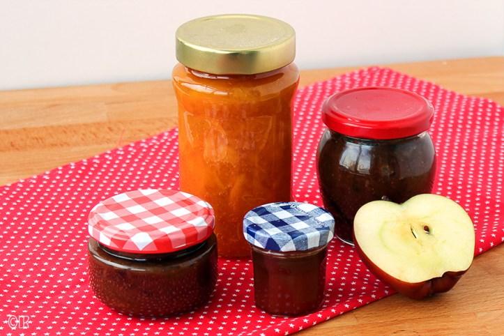 Op een rood-wit tafelkleedje staan 4 potten jam en een halve appel. Pectine is de stof die de jam bindt.