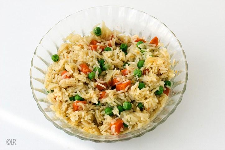 Schaal met rijst waarin de doperwtjes en wortel goed te zien is.
