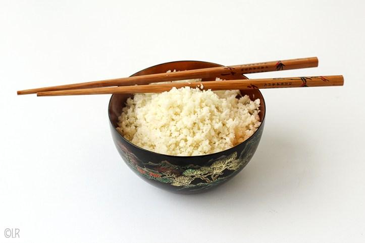 Schaaltje imitatie rijst gemaakt van bloemkool. Er bovenop twee eetstokjes.