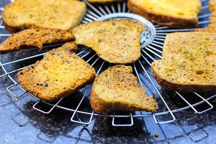 Op een rooster liggen een paar sneetjes geroosterd knoflookbrood af te koelen.