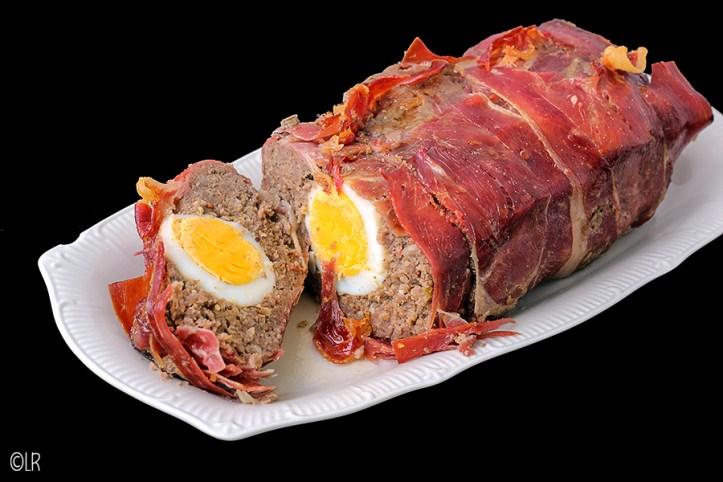 Op een schaaltje een gehaktbrood (meat loaf) ingepakt in rauwe ham en met hardgekookte eieren.