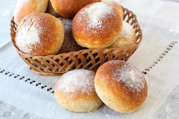 Een mandje met 12 ovenverse zachte lichtbruine broodjes met meel bestoven.