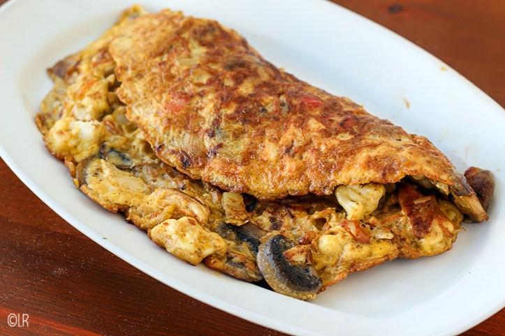 Een schotel met een goed gevulde omelet met kip en groenten.