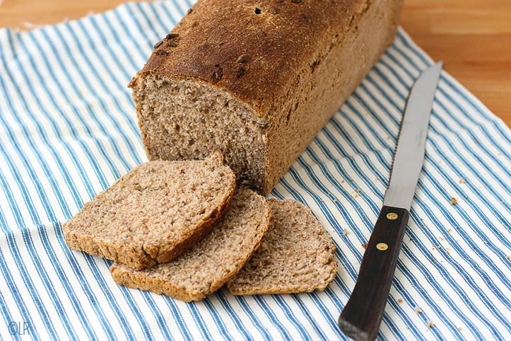 Volkorenbrood met 3 sneetjes brood en een broodmes op een gestreept tafelkleed.