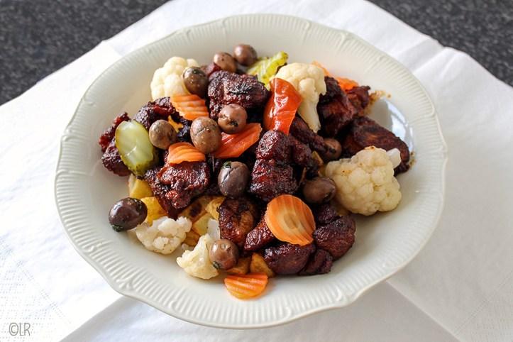 Schotel gebraden varkensvlees met groenten in het zuur, olijven en gefrituurde aardappelblokjes.