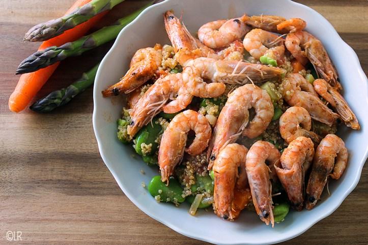Schotel met Quinoa met veel groenten en erop in knoflookolie gebakken garnalen.