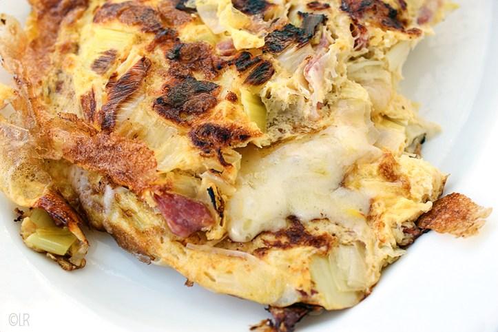 Goed gevulde omelet met prei, spekjes met een kern van gesmolten kaas.