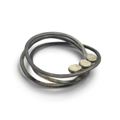 An oxidised silver ribbon folds into an irregular spiral ring, with three dots in palladium white-gold.
