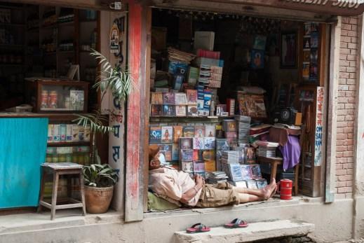 Sklepikarz wypoczywający/pracujący przy swoim biznesie