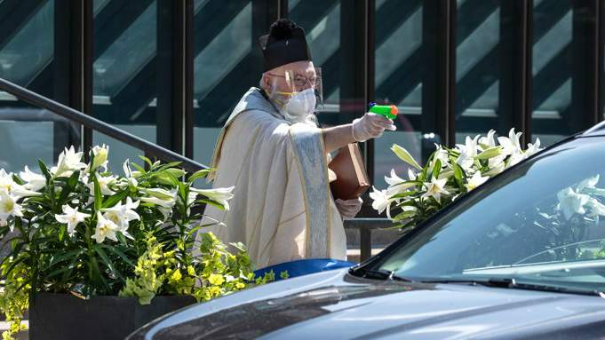 Detroit priest goes viral after using water pistol for socially distanced holy water blessing