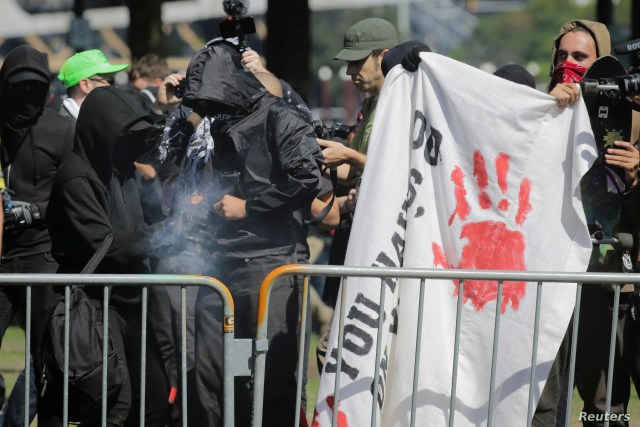 FILE - Antifa counter-protesters, rallying against right-wing group Patriot Prayer, light a smoke grenade in Portland, Oregon, Sept. 10, 2017.
