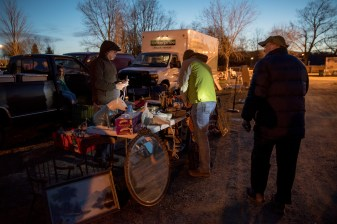 Vendors and early buyers seek to settle a deal in the early morning hours at the Elephant's Trunk flea market, using flashlights to illuminate wares in the dim light in New Milford, CT on Sunday, Apr.10, 2016.