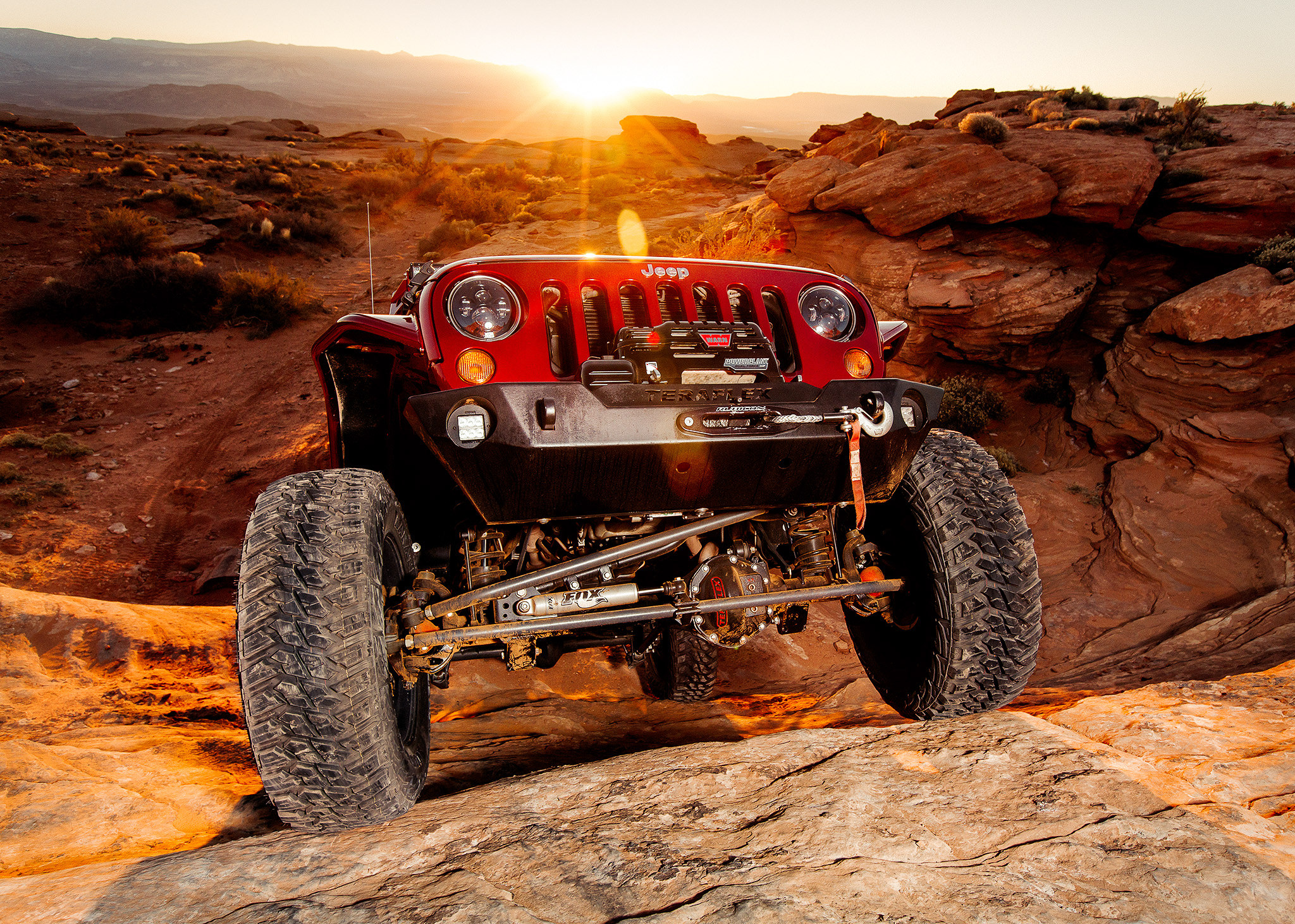 jeep climbing red rock at sunset