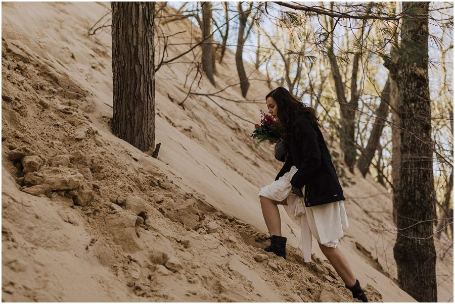 desert inspired elopement bride climbing silver lake sand dunes michigan