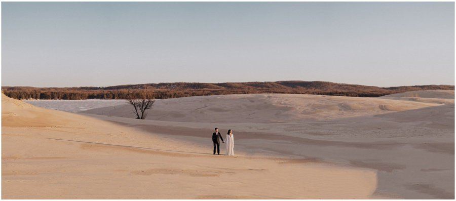 desert inspired elopement couple standing between sand dunes