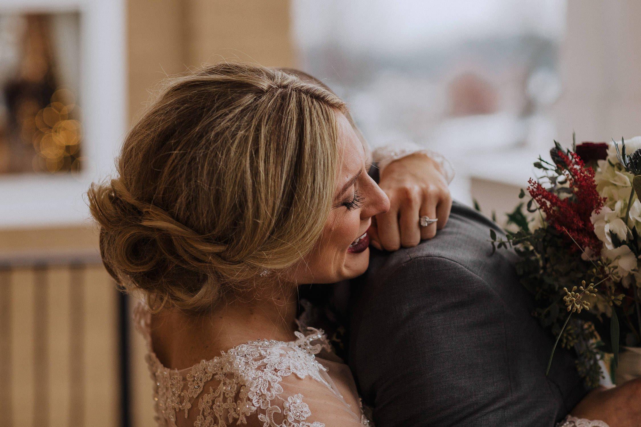 bride crying as she hugs her groom