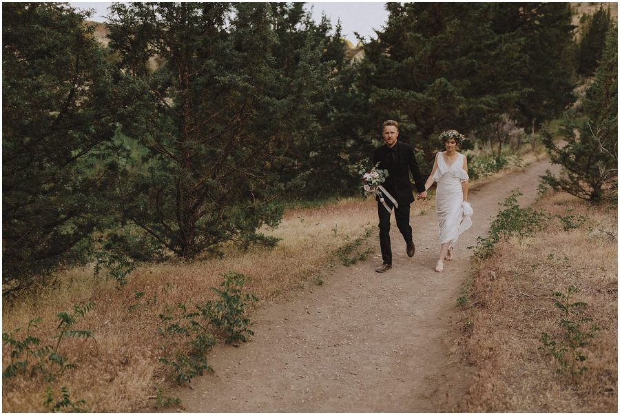 wedding couple walking along a dirt road oregon elopement and wedding photographer kyle szeto