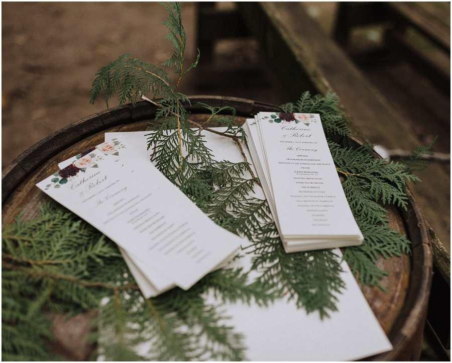 wedding programs sitting on pine needles wisconsin wedding elopement photographer kyle szeto