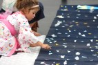 Kids glue stars on the Milky Way.