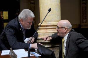 Senator Perry B. Clark (left), D-Louisville, confers with a Senate colleague during a brief recess today on the floor of the Kentucky State Senate.
