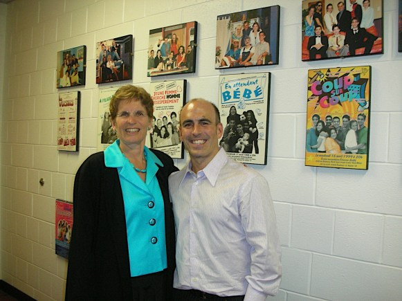 L'enseignant Luc Bernier, directeur du Théâtre Étienne-Brûlé, avec une spectatrice ravie devant le mur d'affiches des pièces présentées à l'école depuis 22 ans.