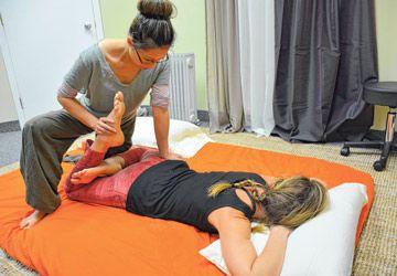 Betty Luong procède à un massage thaï yoga sur Marie, également amatrice de cette pratique.