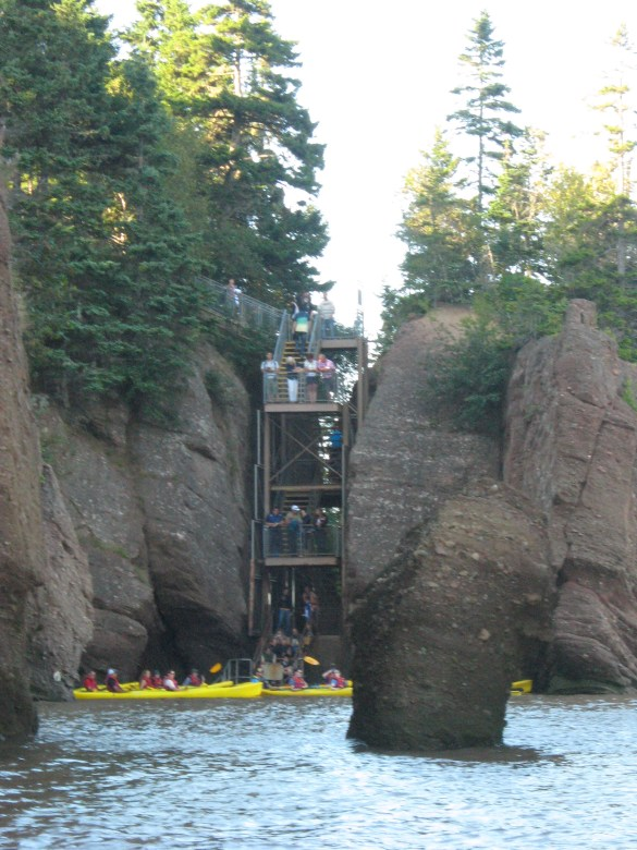 Kayaks à marée haute dans la dernière crique innondée, alors que les autres touristes observent sur un escalier fermé par l'eau: Parc provincial des Rochers Hopewell.