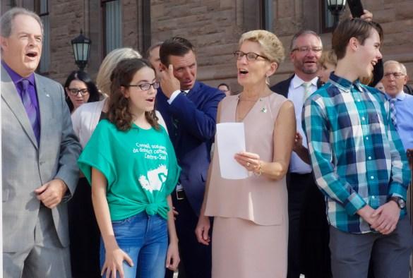 """La Première ministre de l'Ontario Kathleen Wynne, les deux élèves conseillés et le président de l'Assemblée de la Francophonie de l'Ontario Carol Jolin hissent le drapeau franco-ontarien en entonnant l'hymne des Franco-Ontariens et Franco-Ontariennes """"Notre Place"""""""
