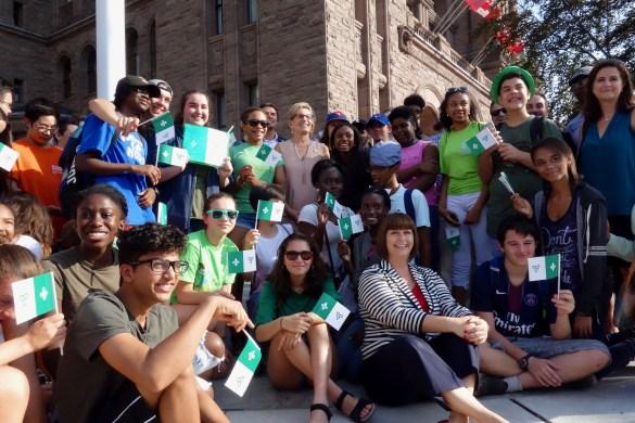 La Première ministre Kathleen Wynne (au centre) et la ministre des Affaires francophones Marie-France Lalonde (assise) entourées d'élèves devant l'esplanade de l'Assemblée législative.
