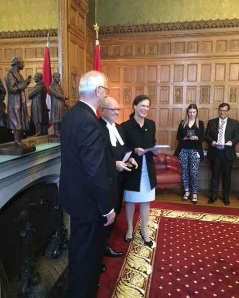 Guy Mignault recevant sa médaille du 150e du président du Sénat, George Furey, en présence de la sénatrice Lucie Moncion. (Photos : Charles Mignault)