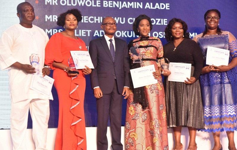 Olakunle Alake (3ème à gauche), directeur général du groupe Dangote Industries Limited, pose avec les lauréats du Long Service Award décerné à Dangote Industries Limited pendant 10 ans; Oluwole Benjamin Alade (à gauche); Olayinka Bolanle Akinola (2e à gauche); Directeur exécutif du groupe, Opérations commerciales du groupe, Dangote Industries Limited, Halima Dangote (3ème à droite); Uchechukwu Chielozie (2e à droite) et Juliet Oshagbemi, responsable de l'apprentissage et du développement de groupes à l'Académie Dangote, de Dangote Industries Limited