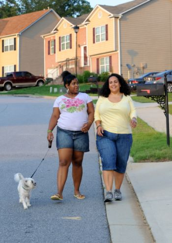 """In this July 11, 2011 photo, Stormy Bradley, right, and her daughter Maya, 14, walk their dog Bubbles in their neighborhood in Atlanta. Maya, who is 5'4"""" tall and weighs about 200 lbs., is part of an anti-obesity ad campaign in Georgia. A provocative article in a prominent medical journal argues parents of extremely obese children should lose custody because they can't control their kids' weight. (AP Photo/Erik S. Lesser)"""