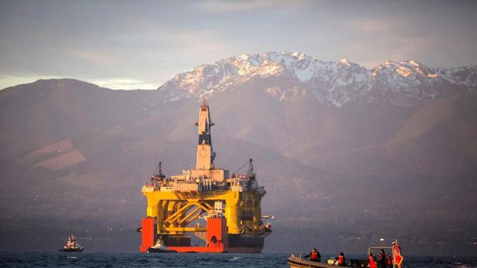 FILE - In this April 17, 2015 file photo, with the Olympic Mountains in the background, a small boat crosses in front of the Transocean Polar Pioneer, a semi-submersible drilling unit that Royal Dutch Shell leases from Transocean Ltd., as it arrives in Port Angeles, Wash., aboard a transport ship after traveling across the Pacific before its eventual Arctic destination. The U.S. government on Monday gave Shell the final permit it needs to drill for oil in the Arctic Ocean off Alaska's northwest coast for the first time in more than two decades.  (Daniella Beccaria/seattlepi.com via AP, File) MAGS OUT; NO SALES; SEATTLE TIMES OUT; TV OUT; MANDATORY CREDIT