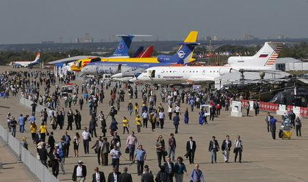 Visitors walk along row of planes and helicopters on display at MAKS International Aviation and Space Salon in Zhukovsky