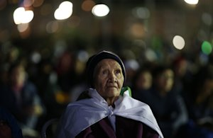 A woman watches a Stations of the Cross performance,…