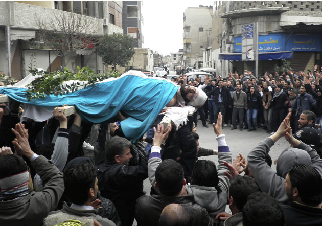 People carry the body of Mohammed al-Mnawi who was allegedly killed by the Syrian security forces on Saturday as they shout anti-government slogans during his funeral in Kfar Suseh area, Damascus, Syr