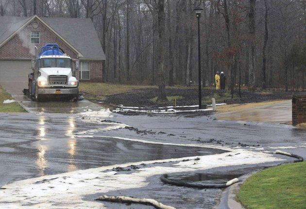 Men wearing protective clothing survey cleanup efforts March 30, 2013 where an underground crude oil pipeline ruptured in the Northwood subdivision in Mayflower, Arkansas.  Exxon Mobil was working to clean up thousands of barrels of oil after the pipeline ruptured causing 22 homes to be evacuated in the area. The Pegasus pipeline, which carries Canadian crude oil from Pakota, Illinois to Nederland, Texas was shut-off Friday after the lead was discovered , the company said in a statement. Photo taken March 30, 2013.    REUTERS/Rick McFarland/Arkansas Democrat-Gazette/Handout (UNITED STATES - Tags: DISASTER ENERGY ENVIRONMENT) NO SALES. NO ARCHIVES. FOR EDITORIAL USE ONLY. NOT FOR SALE FOR MARKETING OR ADVERTISING CAMPAIGNS. NO ONLINE USE. NOT FOR SALE FOR INTERNET DISPLAY. THIS IMAGE HAS BEEN SUPPLIED BY A THIRD PARTY. IT IS DISTRIBUTED, EXACTLY AS RECEIVED BY REUTERS, AS A SERVICE TO CLIENTS