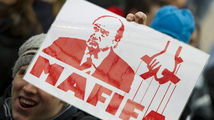 A FC Sion supporter demonstrates with a poster showing FIFA president Sepp Blatter and  the words Mafifa in Sion, Switzerland, Saturday Jan. 7, 2012.  Hundreds of FC Sion fans have protested in their home town against its treatment by FIFA, UEFA and Switzerland's Football Association during a three-year legal dispute. Supporters jeered the mention of Sepp Blatter's name and displayed posters comparing the FIFA President, who comes from nearby Visp, to a Mafia godfather.Under threat of a FIFA suspension, the Swiss FA deducted 36 league points from Sion last month for fielding ineligible players signed in breach of a transfer embargo. Sion is appealing the punishment. UEFA kicked Sion out of this season's Europa League group stage after the players helped beat Celtic in a playoff.   (AP Photo/Keystone/Jean-Christophe Bott)