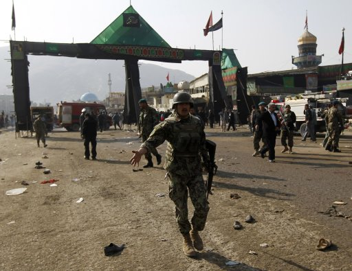 An Afghan National Army soldier disperses the crowd after a suicide attack at a Shi'ite Muslim gathering in Kabul