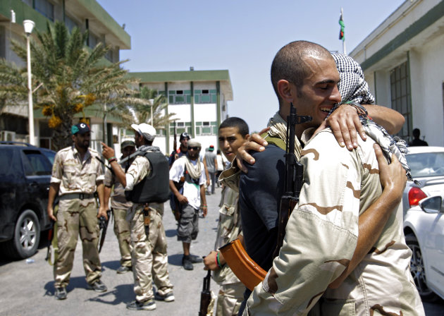 Libyan rebel fighters embrace at the former female military base in Tripoli, Libya, Monday, Aug. 22, 2011. Libyan rebels claimed to be in control of most of the Libyan capital on Monday after their lightning advance on Tripoli heralded the fall of Moammar Gadhafi's nearly 42-year regime, but scattered battles erupted and the mercurial leader's whereabouts remained unknown. (AP Photo/Sergey Ponomarev)