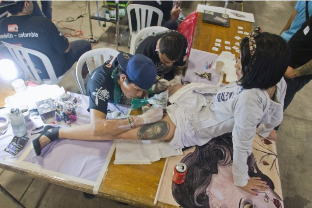 Tattoo artists work on the legs of a woman at the 2nd Annual Tattoo Expo in Medellin