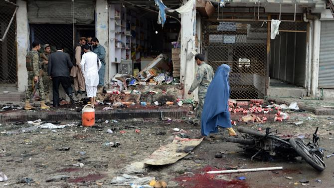A burqa-clad Afghan pedestrian walks past security personnel at the site of a suicide attack outside a bank in Jalalabad on April 18, 2015