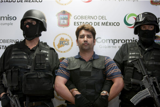 """Mexico state policemen escort Oscar Garcia, 36,  during a presentation to the press in Toluca, Mexico, Thursday, Aug. 11, 2011.  Mexican authorities have arrested Garcia, a crime leader they say has confessed to ordering or being personally connected to more than 600 murders. State of Mexico Attorney General Alfredo Castillo says 36-year-old Oscar Osvaldo Garcia Montoya leads """"The Hand With Eyes"""" organization. (AP Photo/Agencia MVT, Mario Vazquez de la Torre)"""