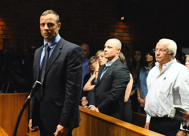 Olympian Oscar Pistorius, foreground, stands following his bail hearing, as his brother Carl, centre, and father Henke, right, look on,  in Pretoria, South Africa, Tuesday, Feb. 19, 2013. Pistorius fi