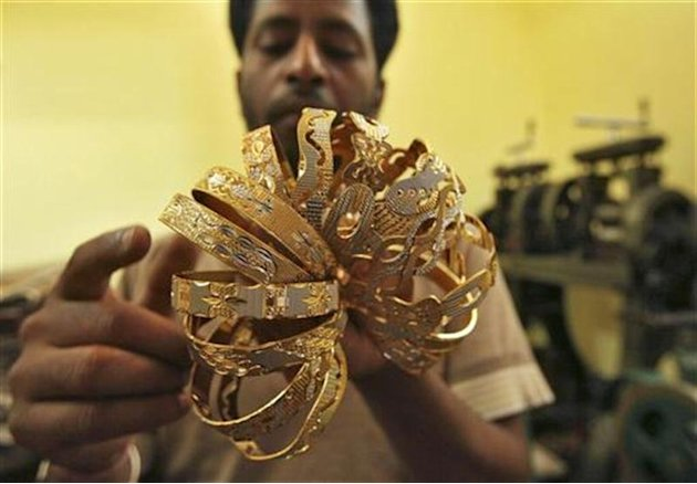 A worker counts gold bangles at a jewellery-making workshop in Jammu