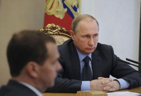 Russian President Putin attends meeting with members of government with PM Medvedev seen in foreground in Moscow