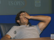 Rafael Nadal of Spain reacts to pain during a press conference after his match against David Nalbandian of Argentina during the U.S. Open tennis tournament in New York, Sunday, Sept. 4, 2011. Answering questions in Spanish, Nadal suddenly started grimacing in pain. He tilted his head back, covered his face with his arm. After a few nervous moments, Nadal popped back up. A simple leg cramp, he insisted. (AP Photo/Andrzej Kentla)