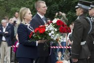 U.S. Secretary of State Hillary Rodham Clinton pays her respects at the Freedom Monument with Latvian Foreign Minister Edgar Rinkevics in Riga June 28, 2012. REUTERS/Haraz N. Ghanbari/Pool